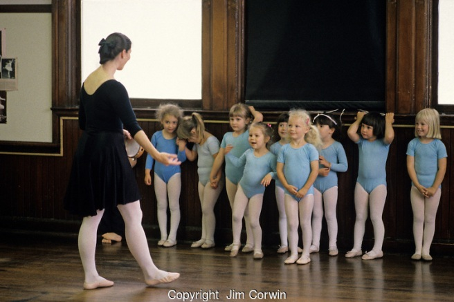 Young ballet dancers at a ballet class standing against the wall listening to the instructions from the ballet teacher